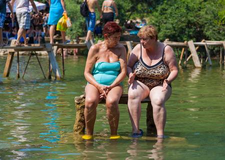 Kravice WASSERFÄLLE, Bosnien und Herzegowina - 10. August: Zwei Frauen sitzen auf Steinbank am 10. August 2012 um Kravice Wasserfälle in BH. Es wird häufig von Touristen aus Medjugorje und Mostar besucht.