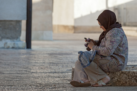 SARAJEVO, BOSNIA AND HERZEGOVINA - AUGUST 12, 2012: Muslim woman sits on the street holding the cell phone in her hand.