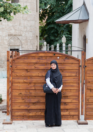 SARAJEVO, BOSNIA AND HERZEGOVINA - AUGUST 11, 2012: Muslim woman wearing traditional clothing stands on the street.