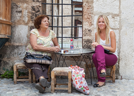 SARAJEVO, BOSNIA AND HERZEGOVINA - AUGUST 11, 2012: Two women sit and drink in front of the house on Bascarsija, the old town, very popular tourist place.