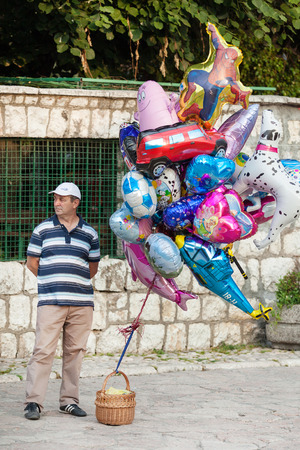 SARAJEVO, BOSNIA AND HERZEGOVINA - AUGUST 13, 2012: Man sells helium balloons on Bascarsija, the old town, very popular tourist place.