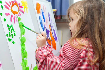 Cute little blond girl holding brush and painting on paper photo