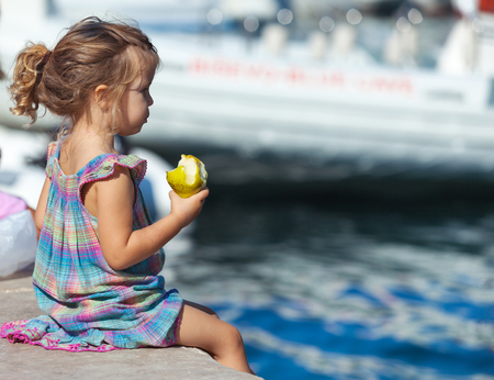 Little blond girl sits on the dock with pear in her hand. photo