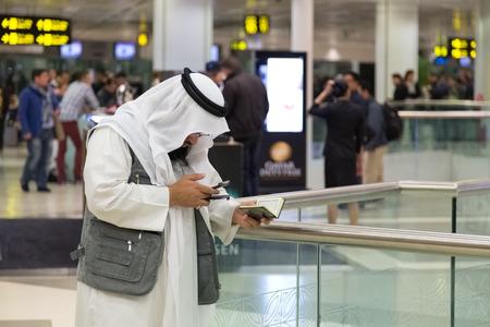 kuran: DOHA, QATAR - 18 feb 2014: uomo musulmano che porta i vestiti tradizionali in possesso di Kuran e guardando il cellulare a Doha International Airport, l'unico aeroporto commerciale in Qatar.