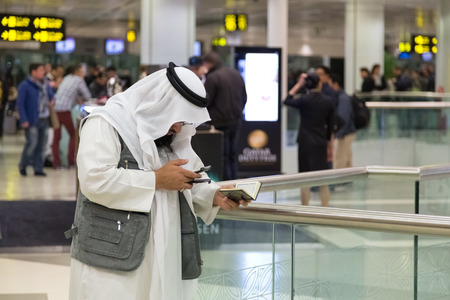 kur'an: DOHA, QATAR - FEBRUARY 18, 2014: Muslim man wearing traditional clothes holding Kuran and looking at cell phone at Doha International Airport, the only commercial airport in Qatar. Editorial