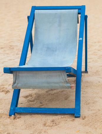 Empty blue deckchair at sandy beach. photo