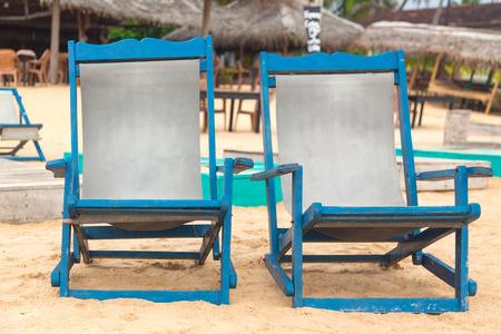 Two empty blue deckchairs at sandy beach. photo