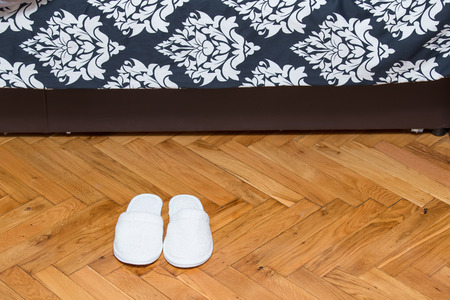 Slippers on wooden floor parquet in front on bed in house photo