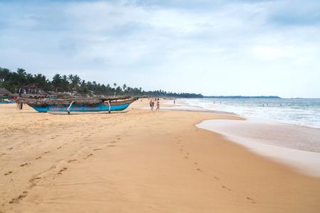 HIKKADUWA, SRI LANKA - FEBRUARY 20, 2014: Tourists enjoys walking and swimming at Hikkaduwa beach well known tourist international destination for board surfing.