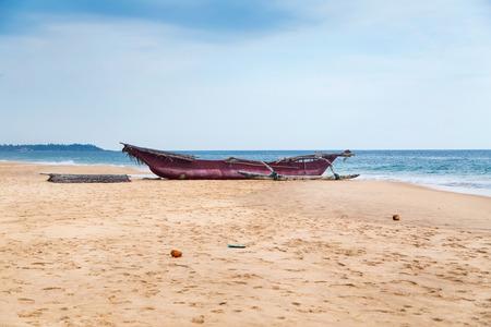 Traditional Sri Lankan fishing boat on empty sandy beach. photo