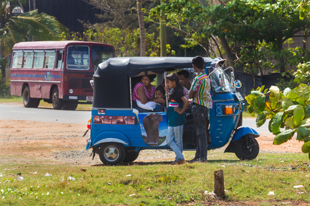 tuk tuk: WELIGAMA, SRI LANKA - MARCH 7, 2014: Local people in tuk tuk vehicle. Tourism and fishing are two main business in this town.