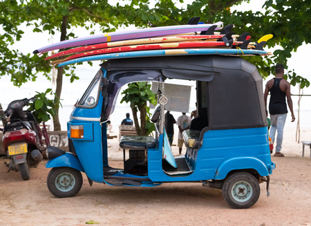 tuk: WELIGAMA, SRI LANKA - MARCH 7, 2014: Blue tuk tuk vehicle transporting surfboards on the roof. Tourism and fishing are two main business in this town. Editorial