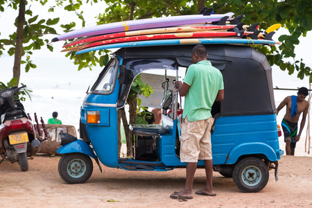 tuk tuk: WELIGAMA, SRI LANKA - MARCH 7, 2014: Driver stand in front of blue tuk tuk vehicle transporting surfboards on the roof. Tourism and fishing are two main business in this town.