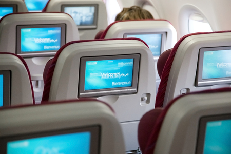 onboard: DOHA, QATAR - FEBRUARY 18, 2014: Economy class seats with entertainment system onboard. Qatar Airways Economy Class was named best in the world in the 2009 and 2010 Skytrax Awards. Editorial