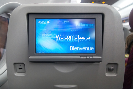 onboard: DOHA, QATAR - FEBRUARY 18, 2014: Economy class seat with entertainment system onboard. Qatar Airways Economy Class was named best in the world in the 2009 and 2010 Skytrax Awards.