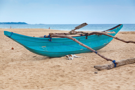 Dog lying in front of the traditional Sri Lankan fishing boat on empty sandy beach  photo