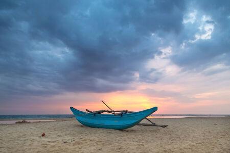 Traditional Sri Lankan fishing boat on empty sandy beach at sunset  photo