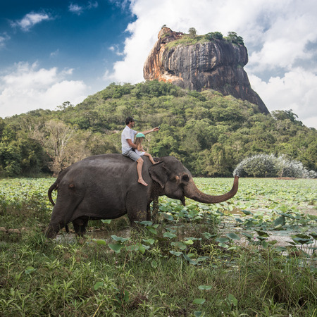 Man and child riding on the back of elephant with rock of Sigiriya as backdrop Фото со стока