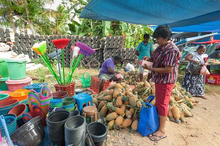 sunday market: HIKKADUWA, SRI LANKA - 23 de febrero 2014: mujer compra local de vendedor ambulante. El mercado de los domingos es una gran manera de ver la vida local de Hikkaduwa cobran vida junto con delicadeza local Editorial