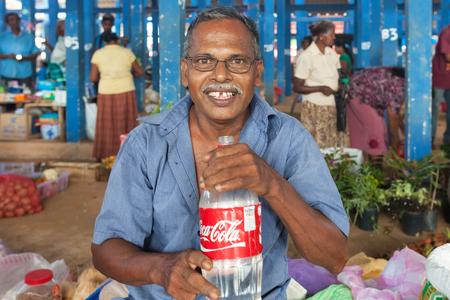 sunday market: HIKKADUWA, SRI LANKA - 23 de febrero 2014: Retrato de proveedor local de la calle con una botella de agua. El mercado de los domingos es una gran manera de ver la vida local de Hikkaduwa cobran vida junto con productos frescos y delicadeza local Editorial