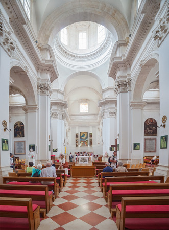 sacramental: DUBROVNIK, CROATIA - MAY 26, 2014: People in church inside the Monastery of the Friars minor. Church is popular place for staging of musical concerts as well as a place of great sacramental importance