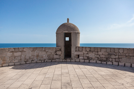 ragusa: Gun turret on old city walls of Dubrovnik (Croatia) with Adriatic sea in background. City walls are on the UNESCO list of World Heritage Sites.