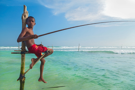 stilt: UNAWATUNA, SRI LANKA - MARCH 9, 2014: Young stilt fisherman at Hikkaduwa Beach. Most real stilt fishermen have been long gone. Today its mainly young boys posing as stilt fishermen for tourists.
