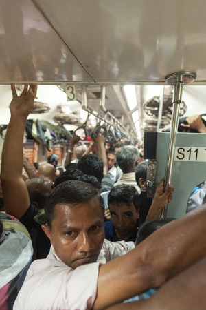 poorly: HIKKADUWA, SRI LANKA - FEBRUARY 22, 2014: Crowded commuter train to Colombo. Trains are very cheap and poorly maintained but its the best option to witness a bit of everyday local life.