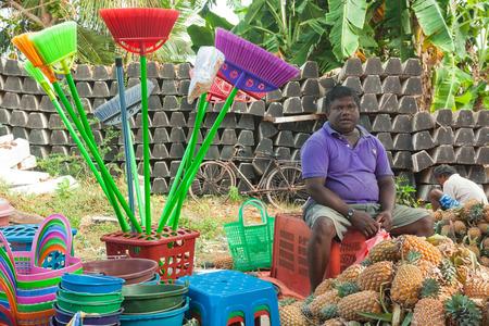 sunday market: HIKKADUWA, SRI LANKA - 23 de febrero 2014: vendedor ambulante local la venta de productos de pl�stico y pi�as. El mercado de los domingos es una gran manera de ver la vida local de Hikkaduwa cobran vida junto con delicadeza local