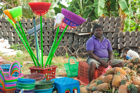 sunday market: HIKKADUWA, SRI LANKA - FEBRUARY 23, 2014: Local street vendor selling plastic products and pineapples. The Sunday market is great way to see Hikkaduwas local life come alive along with local delicacy Editorial