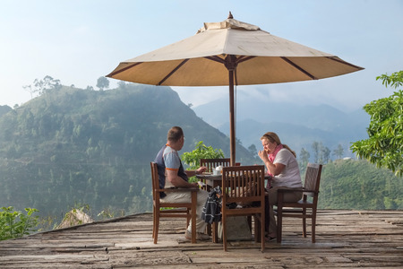 ella: ELLA, SRI LANKA - MARCH 3, 2014: Tourist couple having breakfast at bungalow terrace with amazing view on tea plantations in background. Tea plantations are vital part of Sri Lankan economy since 1850