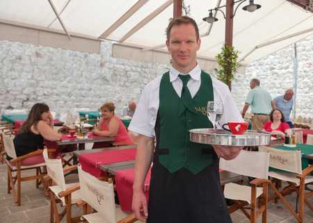 familiy: DUBROVNIK, CROATIA - MAY 26, 2014: Waiter in Poklisar restaurant holding tray and posing for camera.Poklisar is popular small familiy restaurant located by the sea.