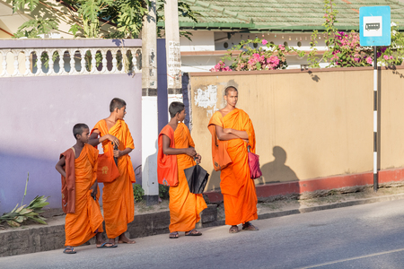 robes: UNAWATUNA, SRI LANKA - MARCH 6, 2014: Group of buddhist monks in traditional orange robes waiting bus at station. 4km inland from Unawatuna the Yatagala Raja Maha Viharaya is temple with a 9m Buddha.