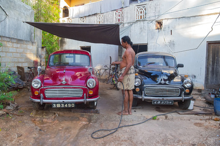 UNAWATUNA, SRI LANKA - MARCH 6, 2014: Local man washing two Morris Minor cars in the yard with water hose. There are estimated to be as many as 4,000 Minors still on the road in Sri Lanka. Editorial