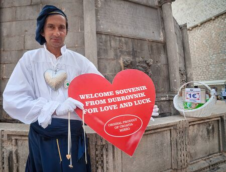 souvenir traditional: DUBROVNIK, CROATIA - MAY 27, 2014: Man wearing old traditional clothes holding big souvenir heart in front of Onofrios fountain. Dubrovnik has many shops selling authentic local craft and souvenirs. Editorial
