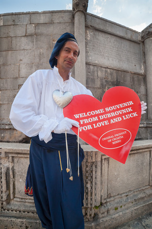 ragusa: DUBROVNIK, CROATIA - MAY 27, 2014: Man wearing old traditional clothes holding big souvenir heart in front of Onofrios fountain. Dubrovnik has many shops selling authentic local craft and souvenirs. Editorial