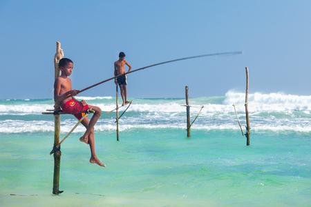 pescador: UNAWATUNA, SRI LANKA - 09 de marzo 2014: pescadores zancos jóvenes en Hikkaduwa Beach. La mayoría de los pescadores zancos reales se han quedado atrás. Hoy en día es principalmente varones jóvenes se hacen pasar por pescadores zancos para los turistas.