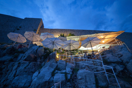 hanged: DUBROVNIK, CROATIA - MAY 27, 2014: Buza beach cafe at night. It is one of the most beautiful bars in Dubrovnik which is hanged on the cliffs right above the sea, with an amazing view of the Adriatic.