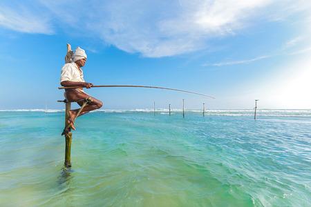 UNAWATUNA, SRI LANKA - MARCH 9, 2014: Elderly stilt fisherman at Hikkaduwa Beach. Most real stilt fishermen have been long gone. Today its mainly young boys posing as stilt fishermen for tourists.