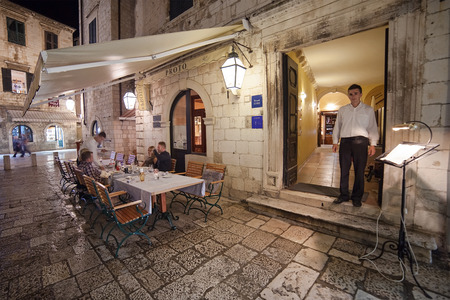 proto: DUBROVNIK, CROATIA - MAY 27, 2014: Waiter standing at the entrance of Proto restaurant. Dubrovnik has many restaurants which offer traditional Dalmatian cuisine and some great wine lists.
