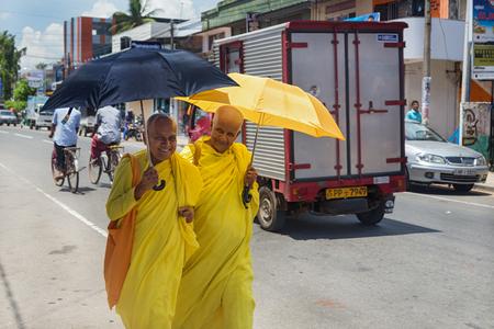 vihara: HIKKADUWA, SRI LANKA - MARCH 4, 2014: Buddhist nuns in yellow robes walk on street of Hikkaduwa. Gangarama Maha Vihara Buddhist temple is worth a visit to experience Hikkaduwas cultural side