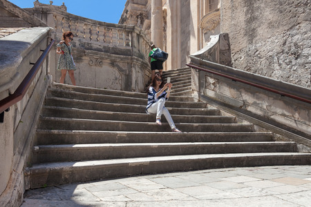 collegium: DUBROVNIK, CROATIA - MAY 28, 2014: Japanese tourists sitting on Jesuits staircase, the grand staircase that leads from Gundulic Square to square in front of Collegium Ragusinum and St. Ignatius Church