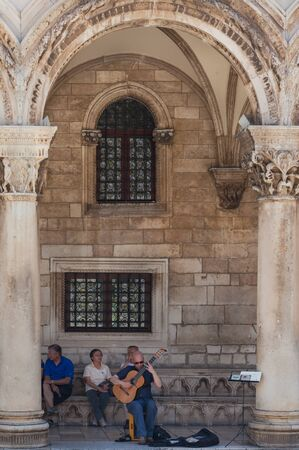 ragusa: DUBROVNIK, CROATIA - MAY 28, 2014: Man plays guitar in front of Rectors palace. Palace used to serve as seat of the Rector of the Republic of Ragusa and today is the museum. Editorial