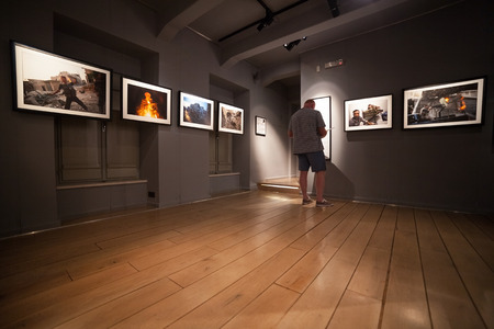 two floors: DUBROVNIK, CROATIA - MAY 26, 2014: Tourist looking at photos in the War photo limited gallery. There is 350m2 of exhibition space on two floors.