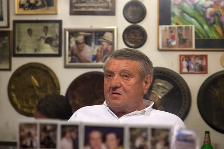 DUBROVNIK, CROATIA - MAY 28, 2014: Hrvoje CIKATO, owner of traditional barber shop Cikato sitting in the chair. Locals often come for chat and to have drink or two with owner.