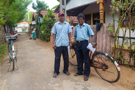 existence: WELIGAMA, SRI LANKA - MARCH 8, 2014: Two postmen delivering post to local people. Sri Lanka Posts has been in existence for more than 209 years and employs more than 17,000 employees.