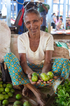 HIKKADUWA, SRI LANKA - MARCH 9, 2014: Local market vendor selling lime. The Sunday market is a fantastic way to see Hikkaduwas local life come alive along with fresh produce and local delicacy.