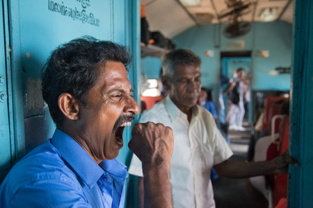 poorly: HIKKADUWA, SRI LANKA - MARCH 12, 2014: Local man yawning in train. Trains are very cheap and poorly maintained but its the best option to witness a bit of everyday local life. Editorial