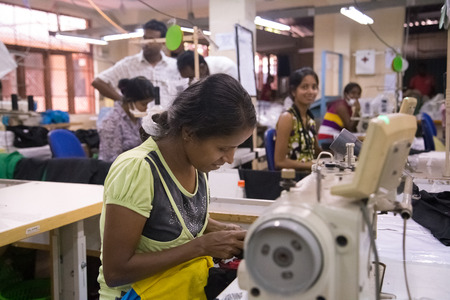 COLOMBO, SRI LANKA - MARCH 12, 2014: Local women working on sewing machine in apparel industry. The manufacture and export of textile products is one of the biggest industries in Sri Lanka. Editoriali