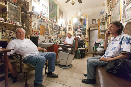 DUBROVNIK, CROATIA - MAY 28, 2014: Hrvoje CIKATO, owner of traditional barber shop Cikato and his friends. Locals often come for chat and to have drink or two with owner.